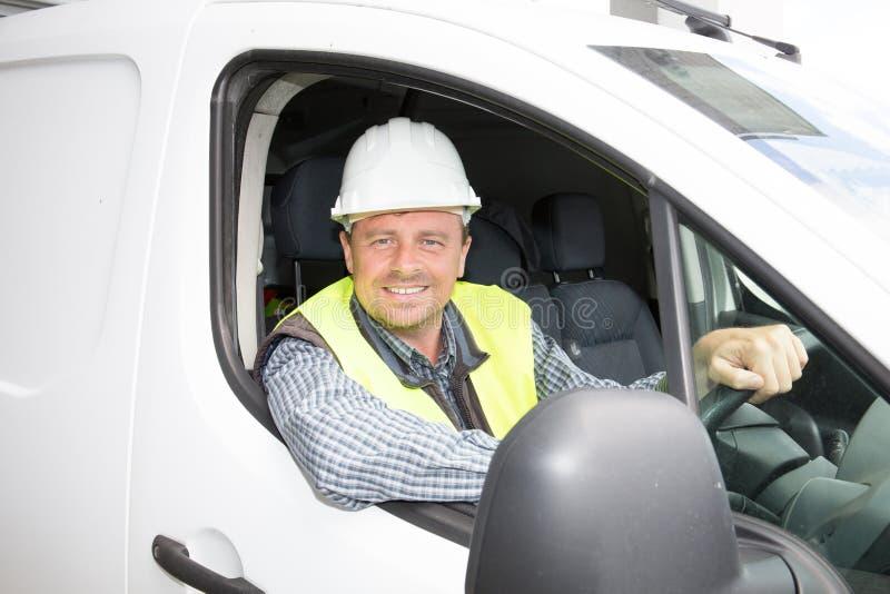 一个建造场所的工匠他的有大微笑的搬运车的 库存照片