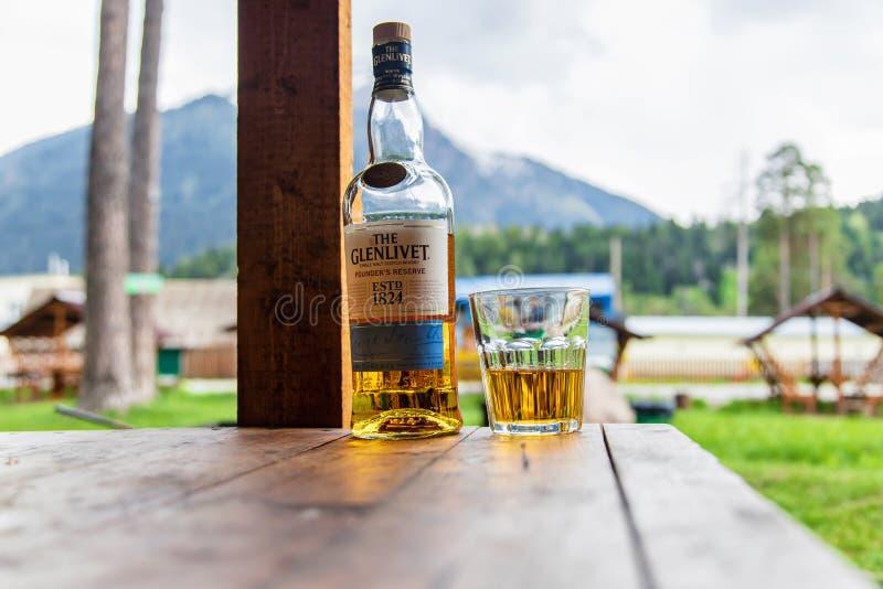 一个开放瓶唯一麦芽威士忌幽谷利韦创建者的在一个木眺望台的储备立场反对山 库存图片