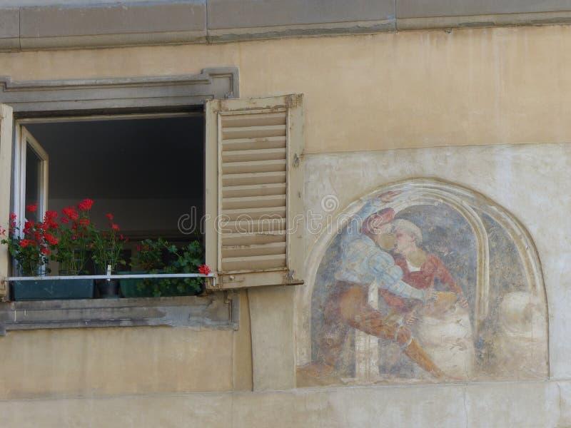 一个开窗口的细节与一个男人和中世纪妇女的附近绘画的在墙壁上 贝加莫在意大利 免版税库存照片