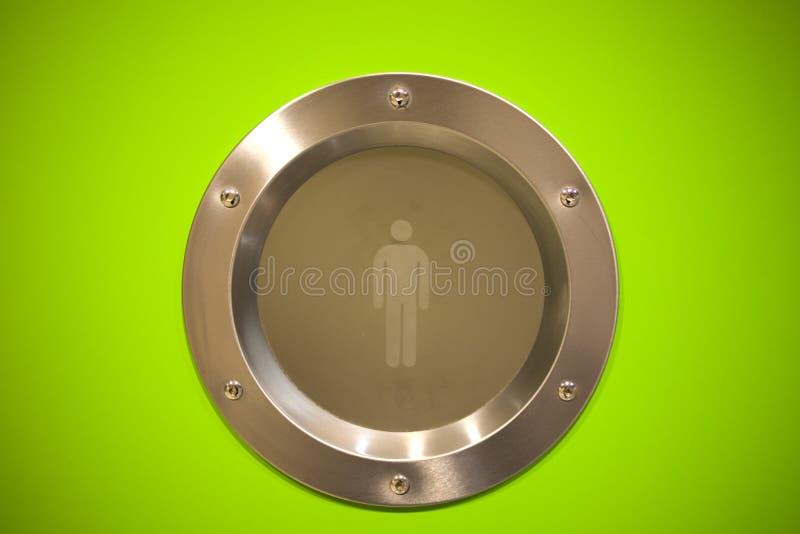 一个异想天开的男盥洗室标志 男盥洗室标志-人的在绿色背景的卫生间象 人平的象设计  免版税库存图片