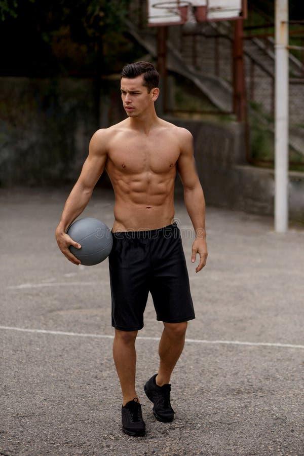 一个强的性感的肌肉年轻人身分的垂直的看法在篮球场的 都市街道背景 r 免版税库存图片