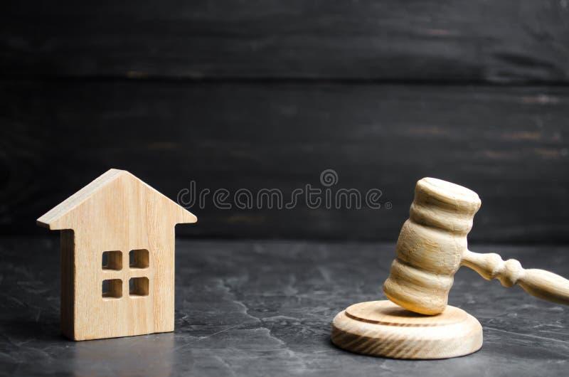 一个微型木房子和法官的锤子 拍卖买/出售房子 牵强的赶出和没收 说明 库存图片