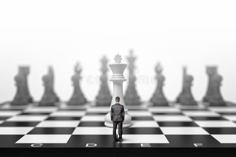 一个微小的商人在一位白国王前面的一杆巨型棋枰站立后面看法的 库存照片