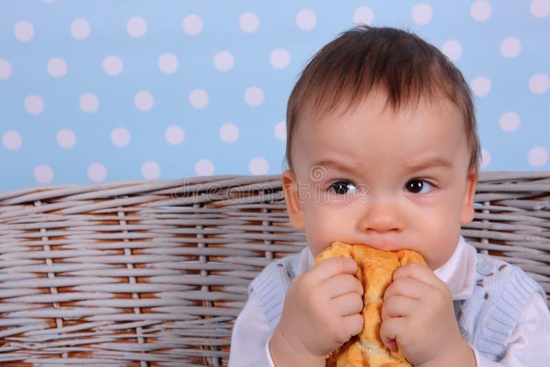 一个微小的孩子吃在从一棵柳条树方平组织的一个干小圆面包 免版税库存照片