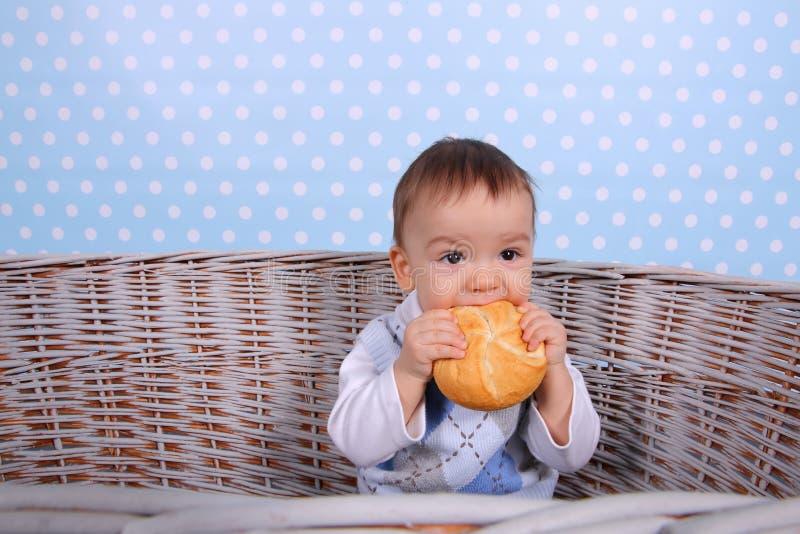 一个微小的孩子吃在从一棵柳条树方平组织的一个干小圆面包 库存照片