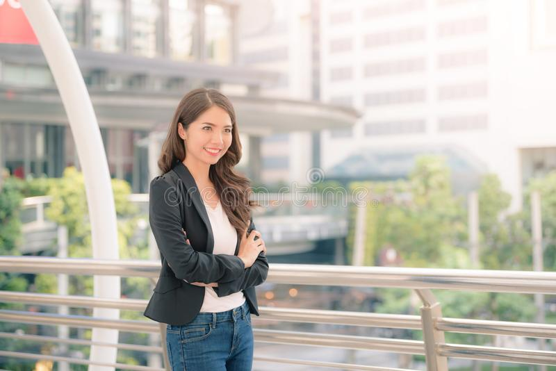一个微笑的亚洲女实业家身分的画象与在被弄脏的城市背景交叉的双臂的 E 免版税库存照片