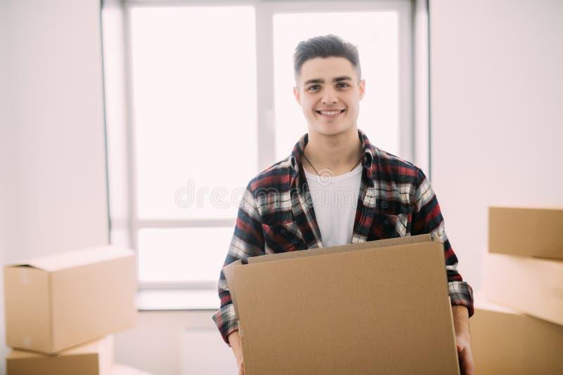 一个微笑的人运载的箱子的画象在新房里 拆迁和移动 免版税库存照片