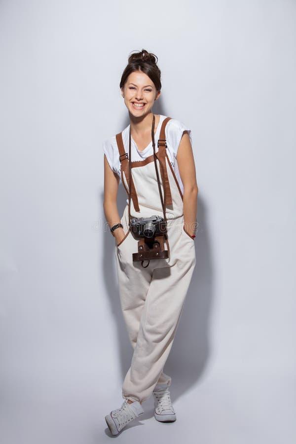 一个微笑的偶然妇女身分和看照相机的全长画象在白色背景的 免版税库存照片