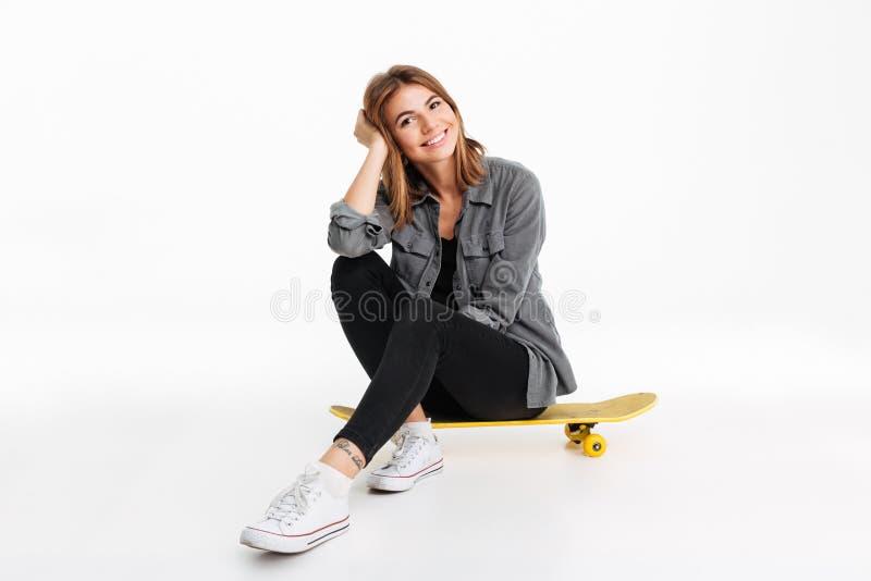 一个微笑的可爱的女孩的画象坐滑板 库存图片