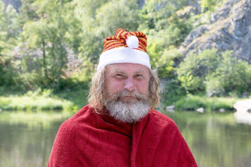 一个微笑的吸引人成人人的画象有作为圣诞老人项目穿戴的胡子的在自然背景中 库存照片