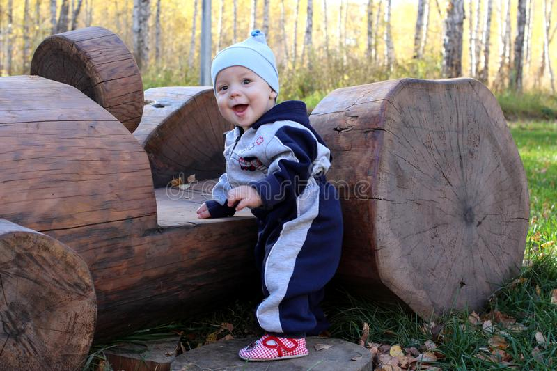 一个微笑的夏天的木日志的一个小孩子与木机器的在公园 库存照片