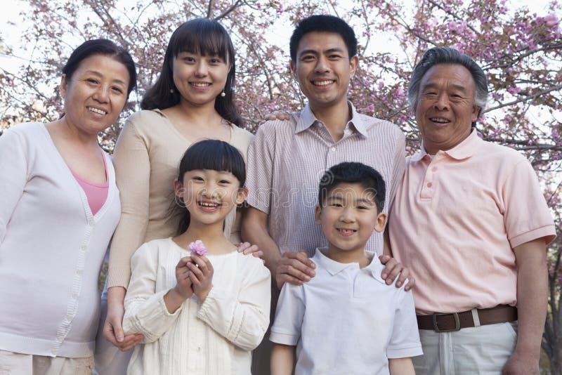 一个微笑的多代家庭的画象在樱桃树和享用公园中的春天 免版税库存图片