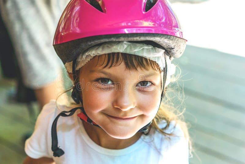 一个微笑的女孩孩子的画象在一个桃红色自行车盔甲特写镜头的5年在街道上 免版税库存照片