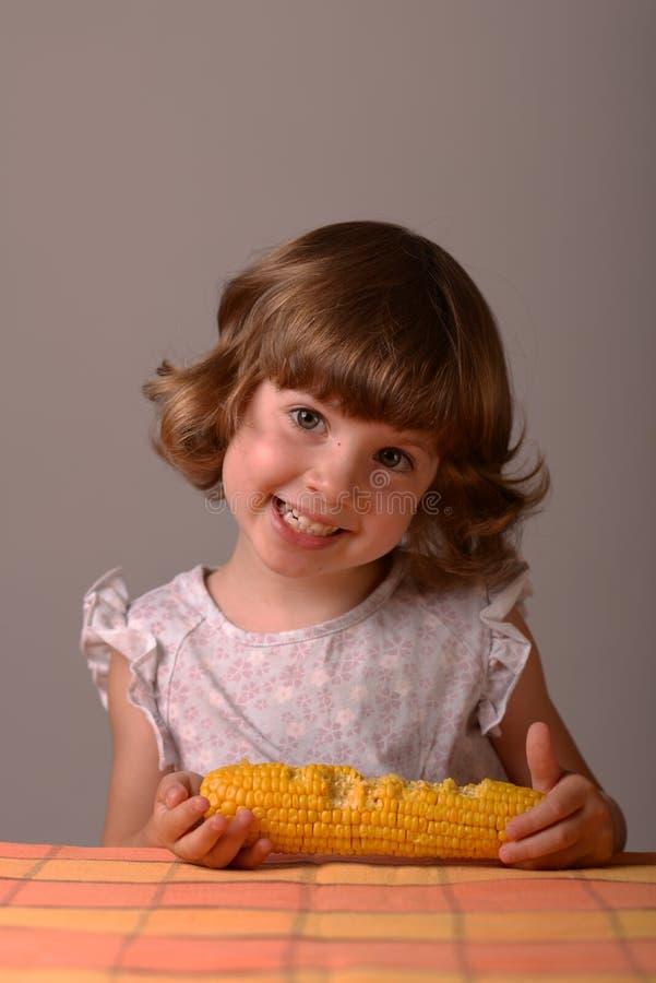 一个微笑的女孩用玉米 免版税库存照片