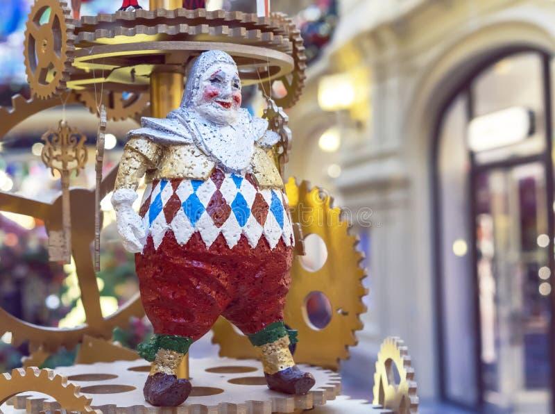 一个微笑的小丑的小雕象一个大时钟机制的背景的 图库摄影