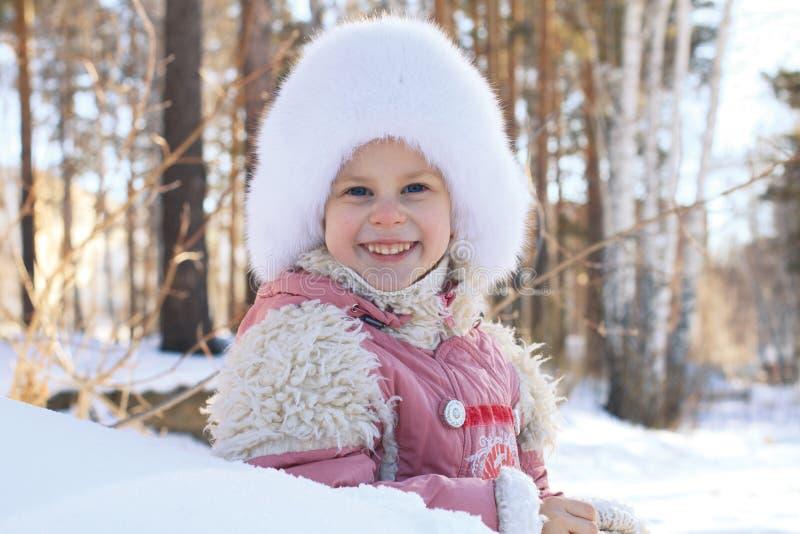 一个微笑的小女孩的画象在冬天 库存照片
