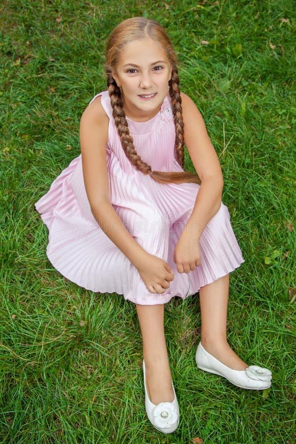 一个微笑的小女孩的画象坐与暴牙的微笑和猪尾发型看照相机的和愉快的绿草 顶层 图库摄影