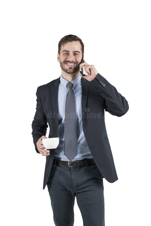一个微笑的年轻商人的画象使用智能手机的 库存图片