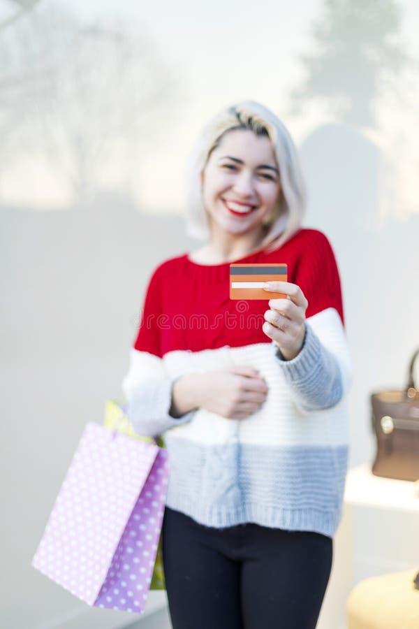 一个微笑的年轻女人身分的正面图在一个购物中心,当拿着信用卡时 库存图片