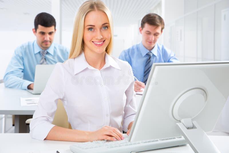 一个微笑的年轻女商人的画象在会议 库存照片