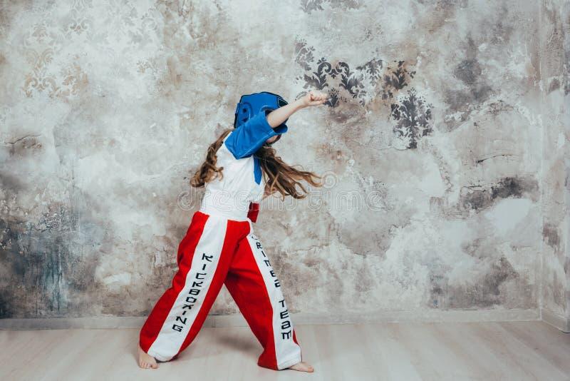 一个微笑的年轻女性跆拳道女孩的画象对难看的东西墙壁 免版税库存图片