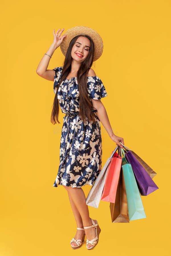 一个微笑的年轻浅黑肤色的男人的全长画象拿着购物袋的夏天帽子和礼服的被隔绝在黄色 免版税库存图片