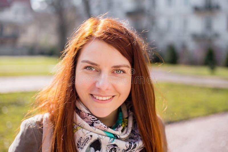 一个微笑的年轻红头发人女孩的接近的画象有看照相机的长发的,当身分户外,春天时 库存照片
