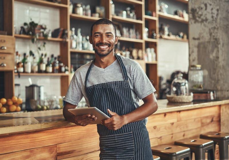 一个微笑的年轻非洲咖啡馆所有者的画象 库存照片
