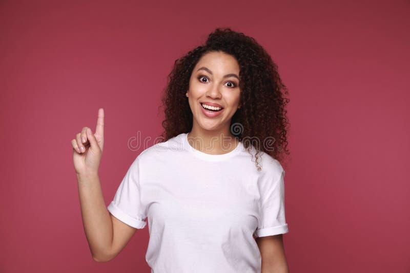 一个微笑的年轻非洲妇女身分的画象被隔绝在背景 看照相机指向 免版税图库摄影