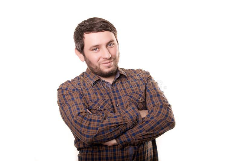 一个微笑的愉快的英俊的中年人的画象有穿镶边衬衣的胡子的看与a的照相机 免版税图库摄影