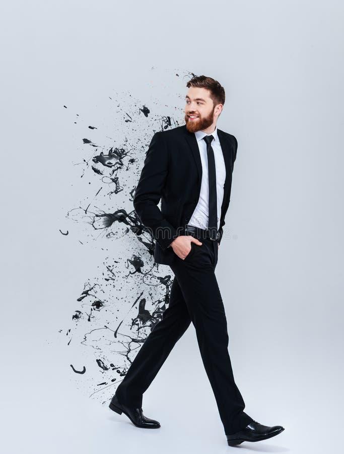 一个微笑的有胡子的商人的画象在黑衣服走的 免版税库存图片