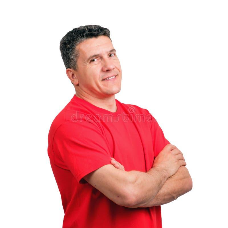 一个微笑的正面人一半的画象在胸口手上转向了穿一件红色不拘形式的T恤杉的照相机与折叠 免版税图库摄影