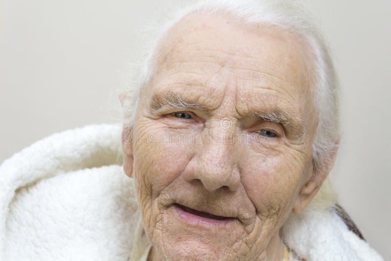 一个微笑的灰发的老妇人的画象一件浴巾的有敞篷的 免版税库存照片