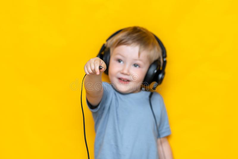 一个微笑的男孩拔去他的耳机和展示插座到在被隔绝的黄色背景的照相机 免版税库存图片