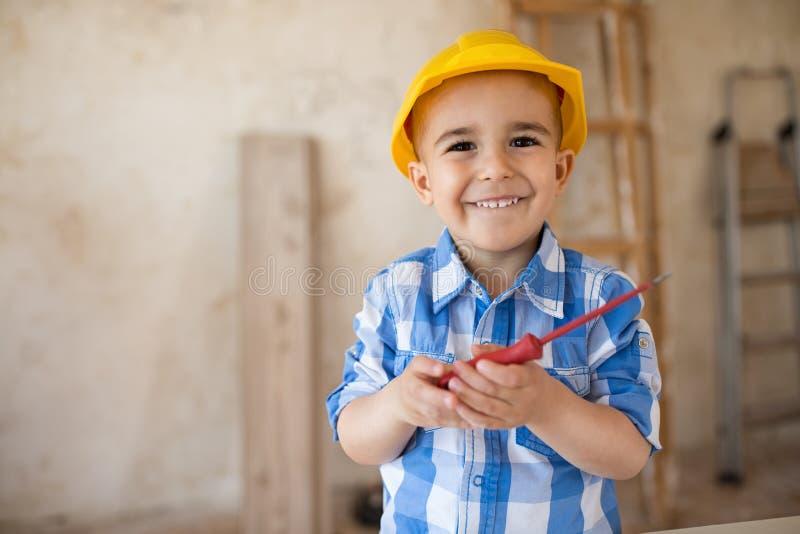 一个微笑的男孩的画象在木匠` s车间 库存照片