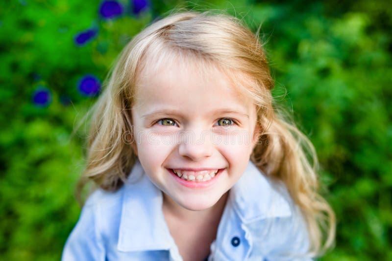 一个微笑的白肤金发的小女孩的特写镜头画象 库存图片