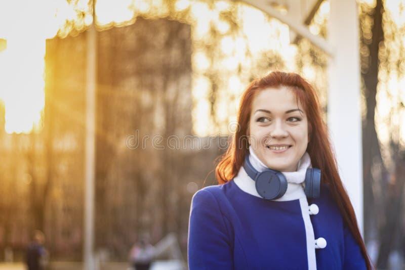 一个微笑的红发女孩的画象有无线耳机的在日落的一件蓝色外套与太阳光芒 作梦年轻 免版税库存图片