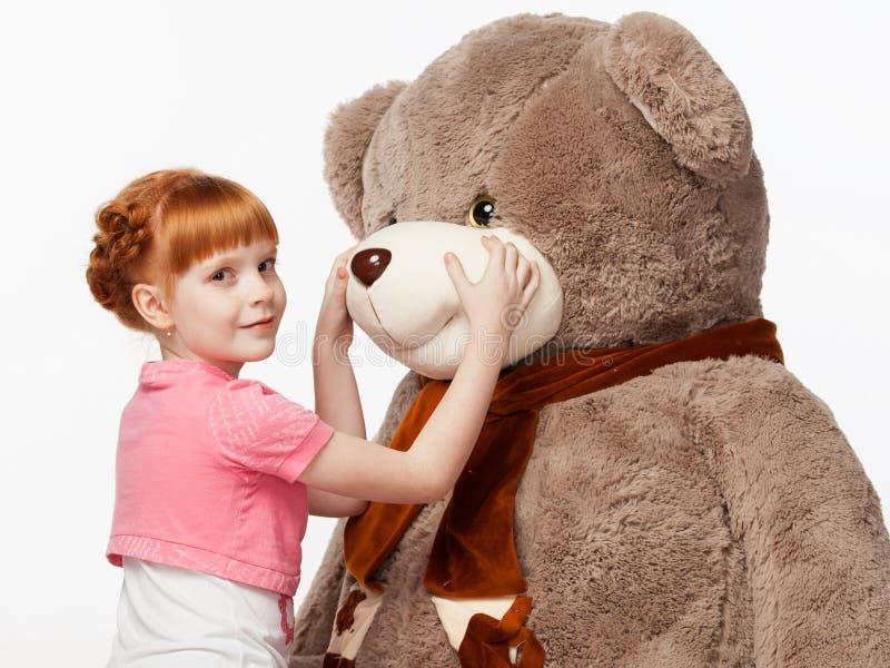 一个微笑的红发女孩的画象拥抱Th的一件桃红色衬衣的 库存照片