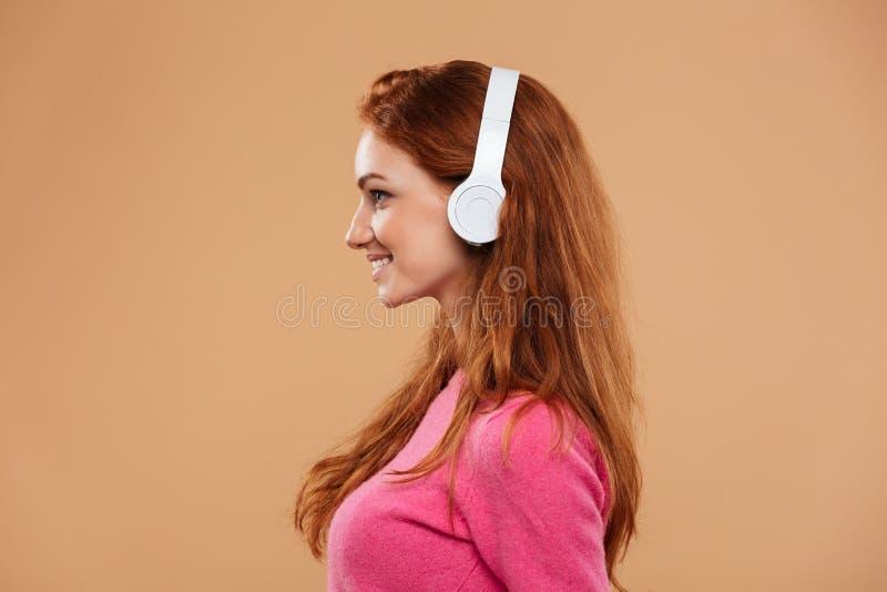 一个微笑的红头发人女孩的画象的侧视图关闭 图库摄影