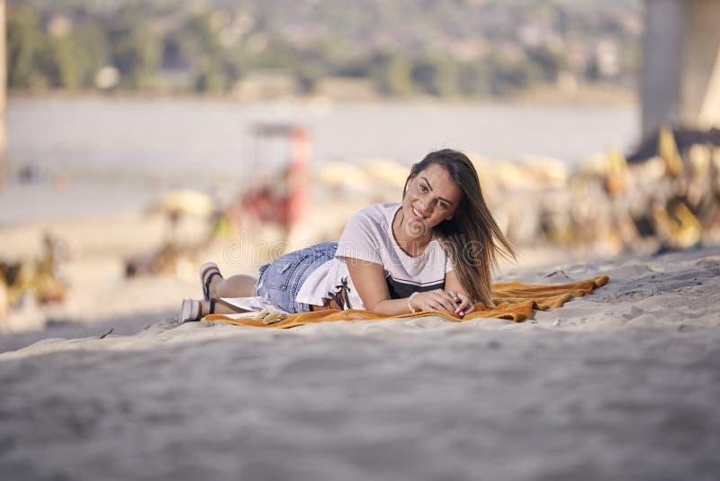 一个微笑的美丽的女孩,摆在看户外照相机靠岸 库存图片