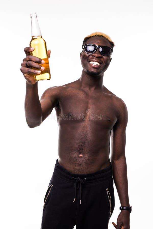 一个微笑的美国黑人的人的画象显示啤酒瓶的太阳镜的被隔绝在白色背景 免版税库存图片