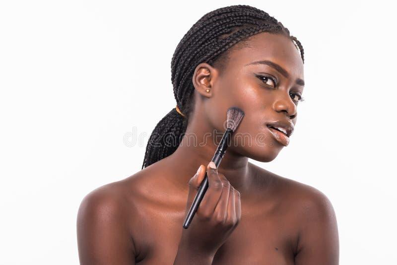一个微笑的美好的一半的秀丽画象申请与刷子的构成和看照相机的赤裸非洲妇女被隔绝  免版税图库摄影