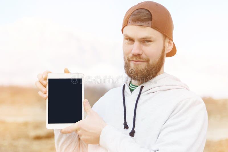 一个微笑的行家的特写镜头画象在一件棕色盖帽室外藏品有保险开关空白的一台白色片剂计算机为 库存照片