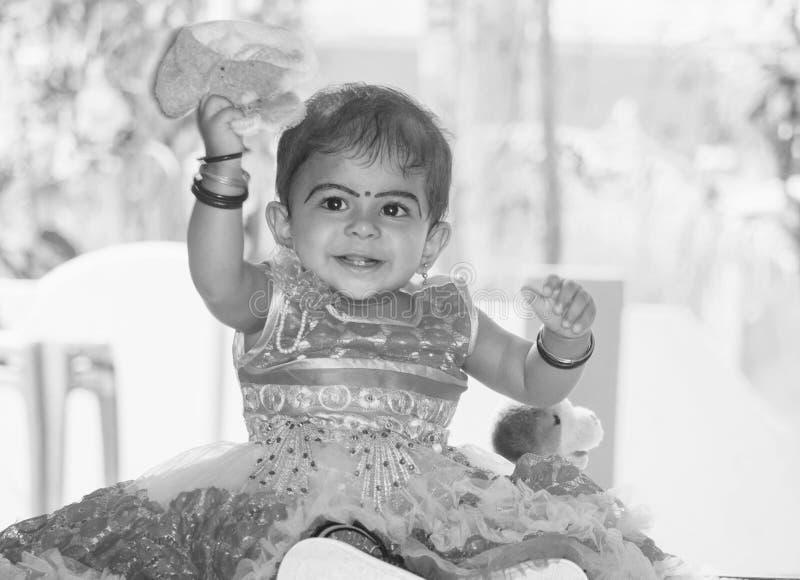 一个微笑的逗人喜爱的印度儿童女孩的一张黑白画象 免版税图库摄影