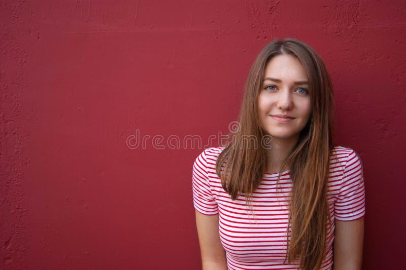一个微笑的青少年的女孩的画象红色背景的 免版税图库摄影