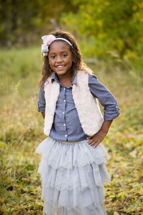 一个微笑的非裔美国人的小女孩的逗人喜爱的室外画象 免版税库存照片