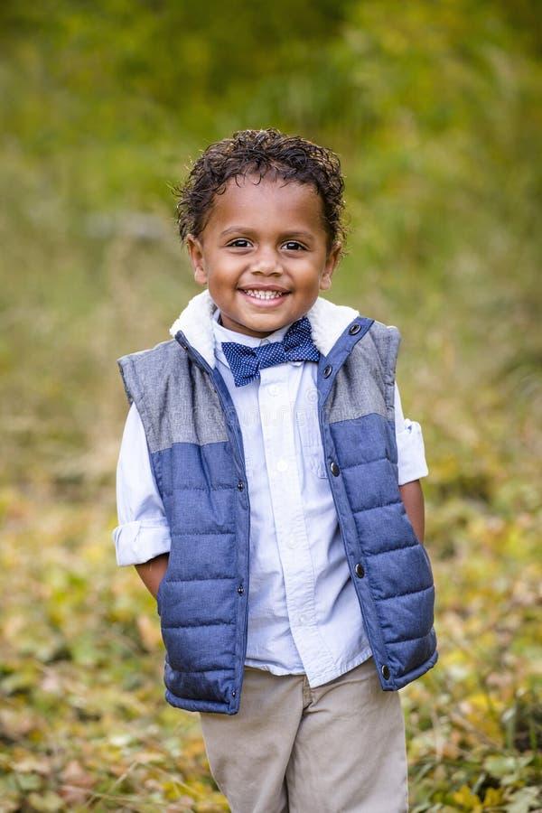 一个微笑的非裔美国人的男孩的逗人喜爱的室外画象 库存图片