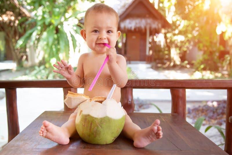 一个快乐和愉快的矮小的一岁的孩子坐从新鲜的绿色椰子的木桌和饮料椰奶通过a 库存照片