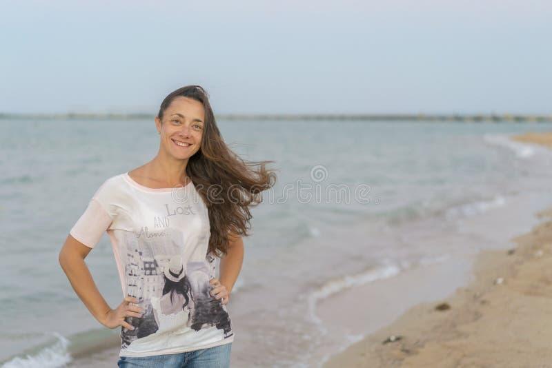 一个快乐的中部年迈的妇女身分的画象在海的 走沿海滨的可爱和愉快的中间年迈的妇女 免版税库存照片