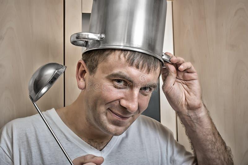 一个快乐的人在他的头上把平底深锅放 免版税库存图片